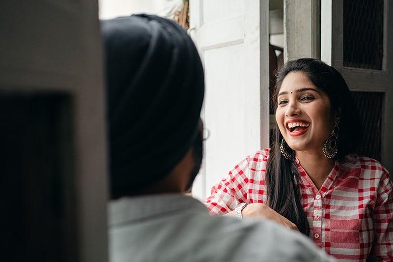eine lachende Frau, die mit einem Mann am Fenster sitzt