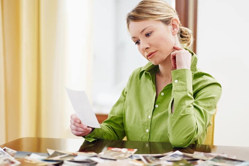 eine nachdenkliche Frau, die Foto schaut, während sie am Tisch sitzt