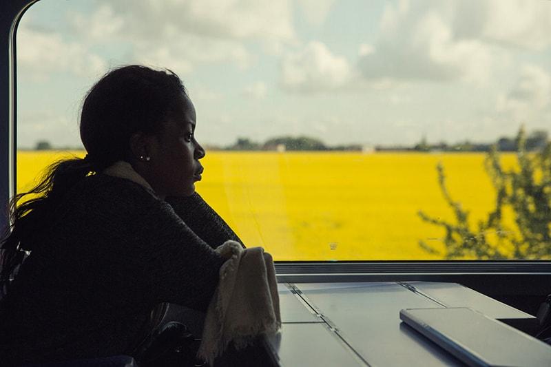 eine nachdenkliche Frau, die alleine im Zug sitzt