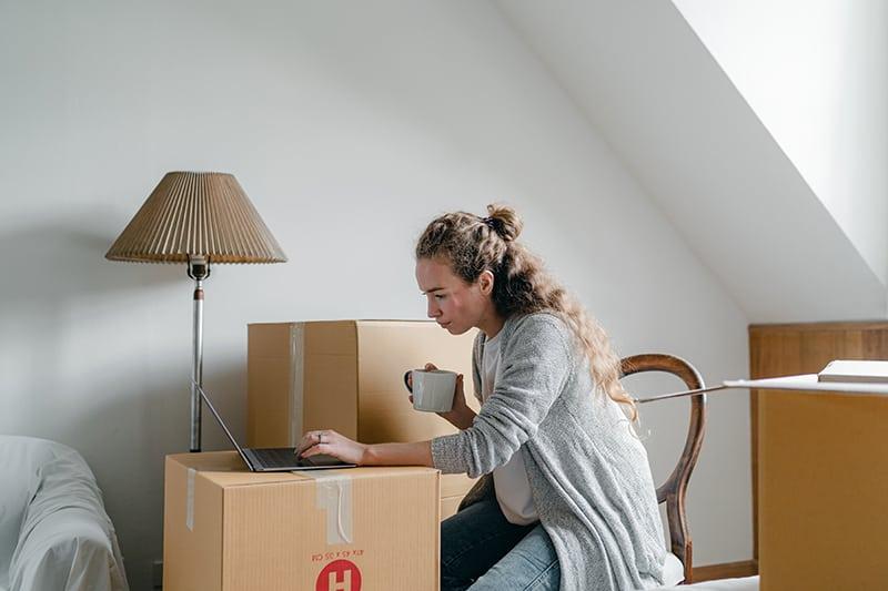 eine nachdenkliche Frau, die auf einem Laptop tippt und eine Pause vom Packen von Sachen in Kartons macht
