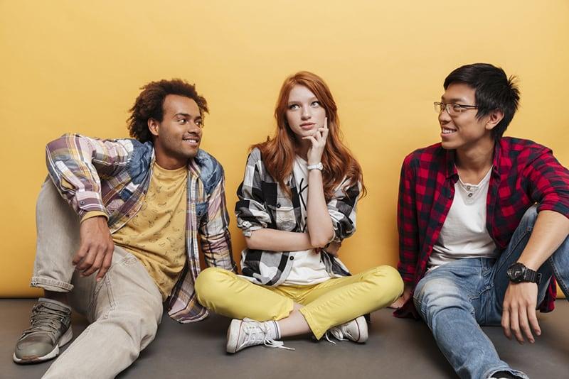eine nachdenkliche Frau, die auf dem Boden zwischen zwei lächelnden Männern sitzt