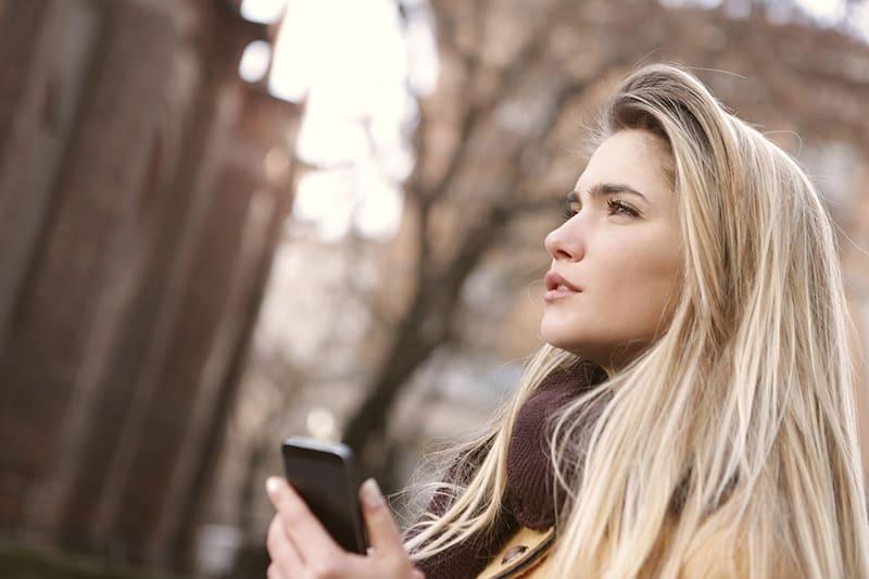 eine nachdenkliche Frau, die das Smartphone hält, während sie im Park steht und gerade schaut