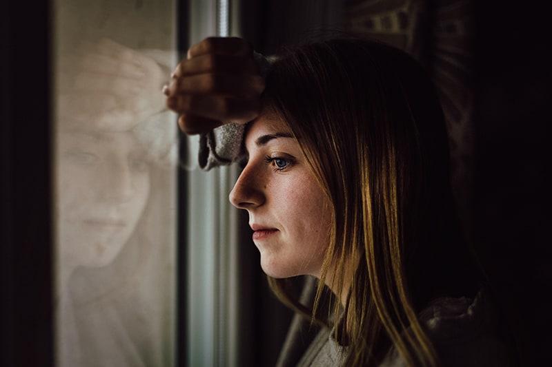 eine nachdenkliche Frau, die sich ans Fenster lehnte und durch das Fenster schaute