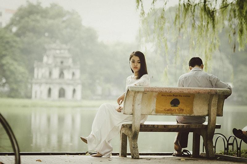 eine nachdenkliche Frau, die fern von einem Mann auf der Bank in der Nähe des Gewässers sitzt