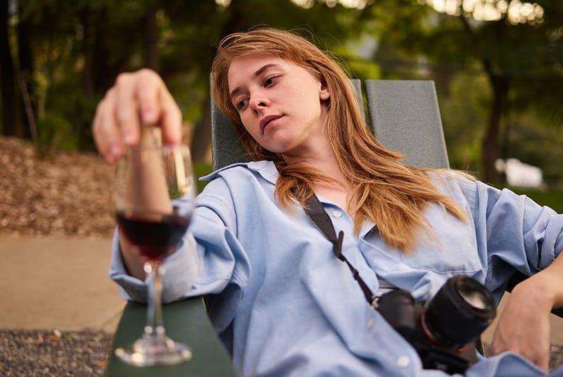 eine nachdenkliche Frau, die auf der Sonnenliege sitzt und ein Glas Wein berührt