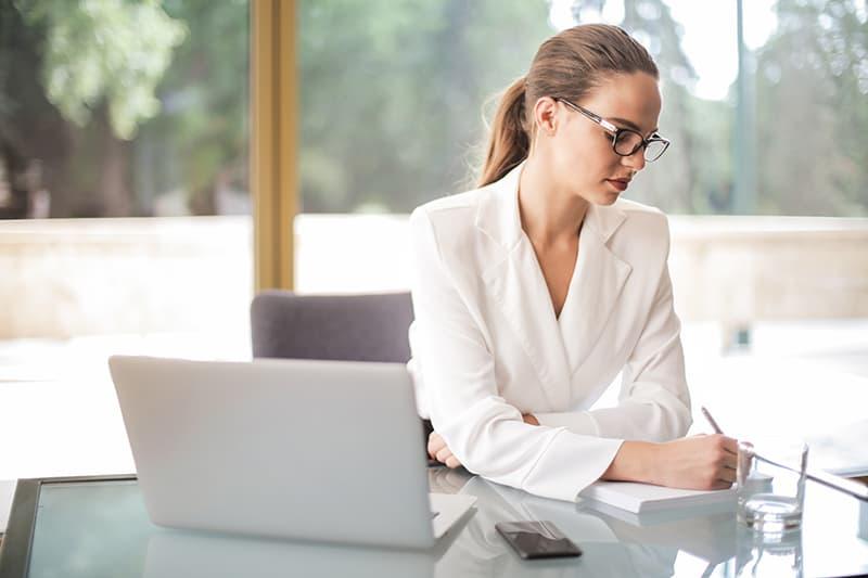 eine nachdenkliche Geschäftsfrau, die in ein Notizbuch schreibt, während sie Pläne macht