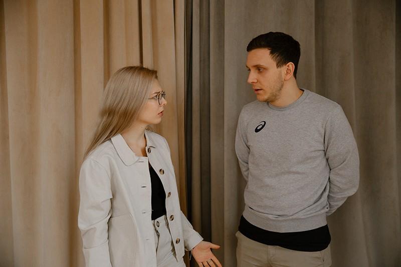 Eine nervöse Frau befragt einen Mann, während sie zusammen in der Nähe des Vorhangs steht