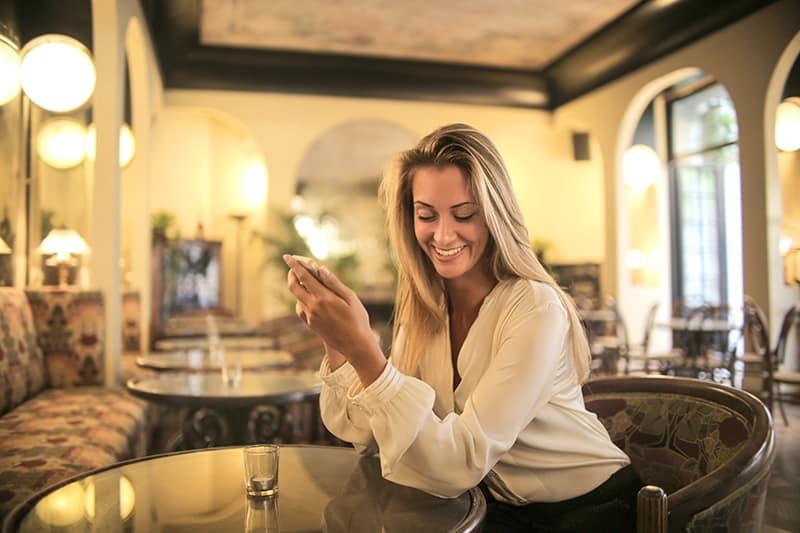 eine positive Frau, die alleine in der Bar sitzt und ein Smartphone hält