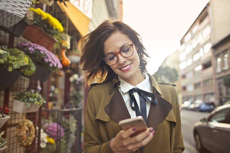 eine positive Frau, die ein Smartphone benutzt, während sie neben dem Blumenladen geht