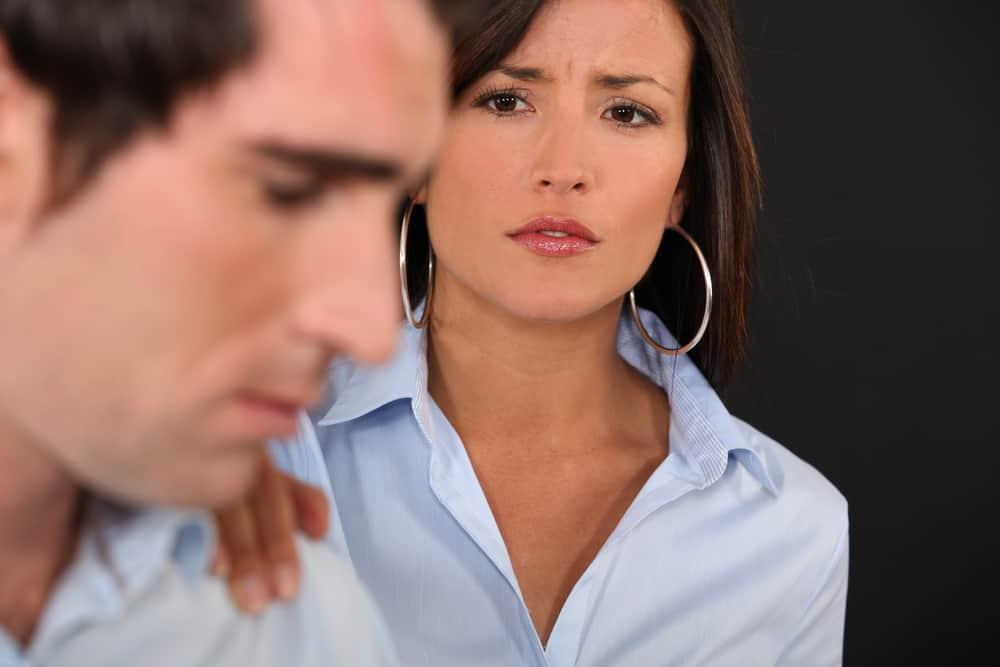 eine schöne Geschäftsfrau mit Schuldgefühlen im Gesicht, die einen Mann an der Schulter hält