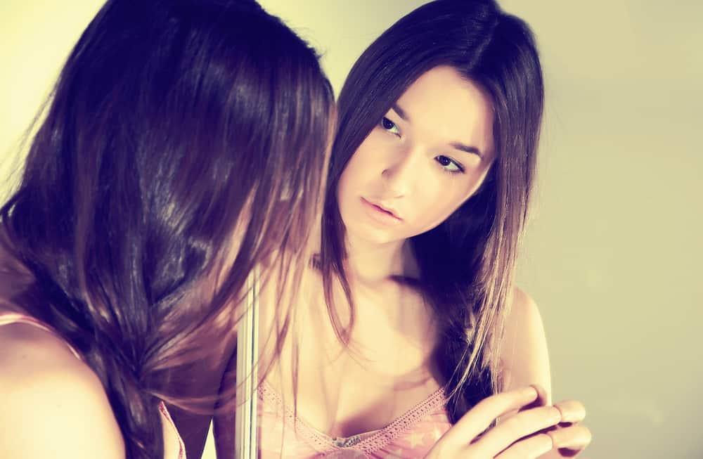 eine schöne traurige Frau, die in den Spiegel schaut