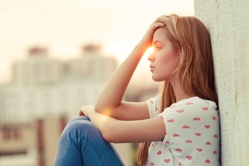 eine traurige Frau, die den Kopf berührt, während sie während des Sonnenuntergangs allein auf dem Dach sitzt
