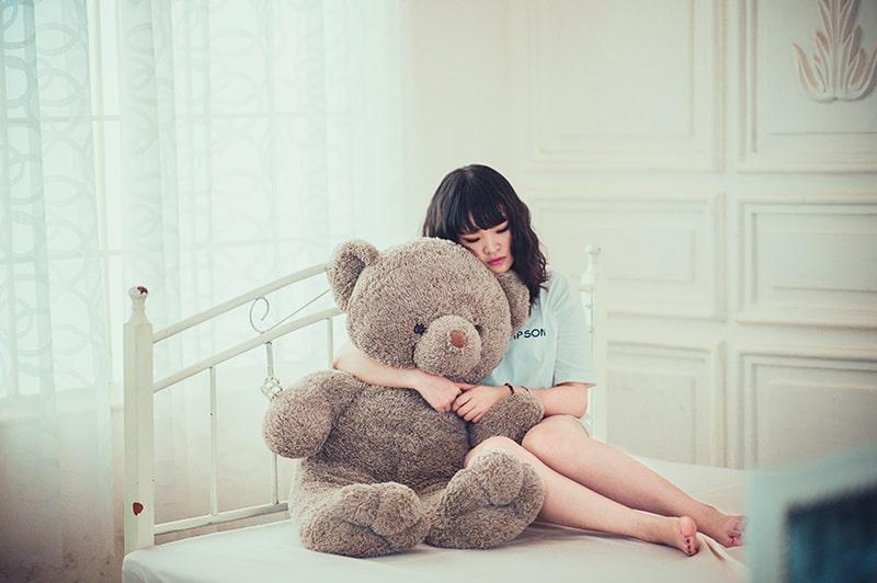 eine traurige Frau, die einen Teddybären umarmt, während sie auf dem Bett sitzt