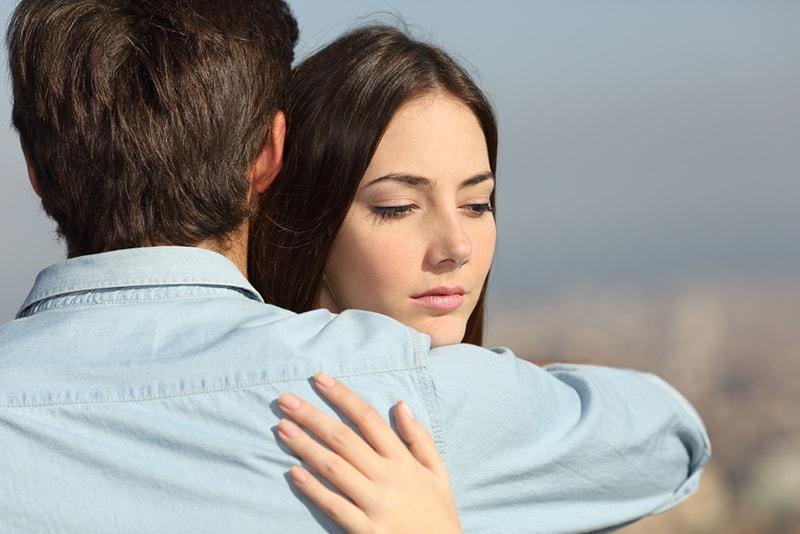 eine traurige Frau, die schaut, ihren männlichen Freund umarmend, während sie draußen steht