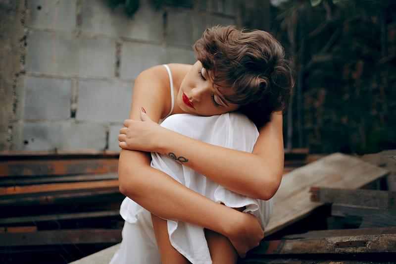 eine traurige Frau, die sich auf die Knie stützte, während sie auf der Treppe saß