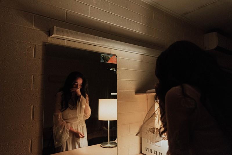 eine traurige Frau, die nachts vor dem Spiegel weint