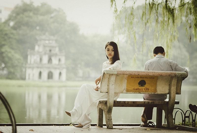 eine traurige Frau, die auf der Bank neben einem Mann in der Nähe des Sees sitzt