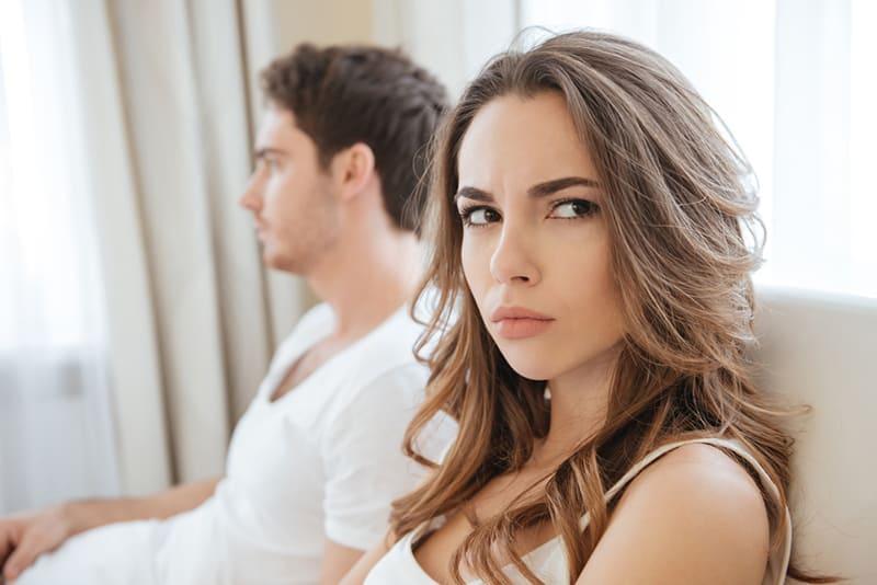 Eine verärgerte Frau sitzt im Bett neben einem Mann, der traurig aussieht