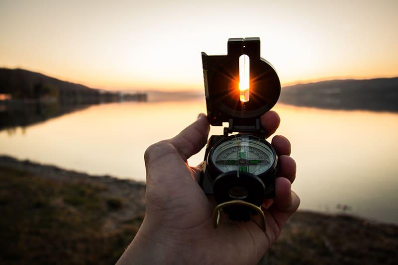 eine verlorene Person, die einen Kompass während des Sonnenuntergangs hält