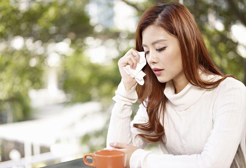 junge Frau, die Tränen mit Gesichtstuch abwischt, während sie draußen am Tisch sitzt