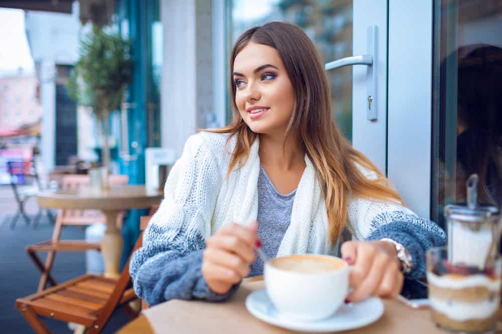 junges attraktives Mädchen, das Kaffee in einem Café trinkt