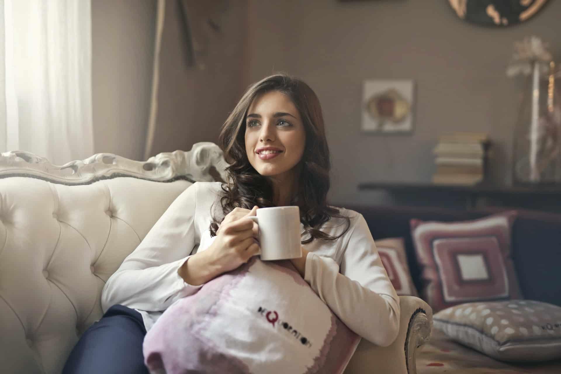 lächelnde Frau, die auf der Couch sitzt und während einer Pause Kaffee trinkt