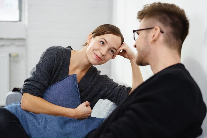 lächelnde Frau, die einen Mann beim Sitzen auf der Couch betrachtet