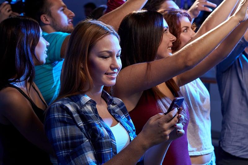lächelnde Frau mit einem Smartphone beim Konzert im Club von Freunden umgeben