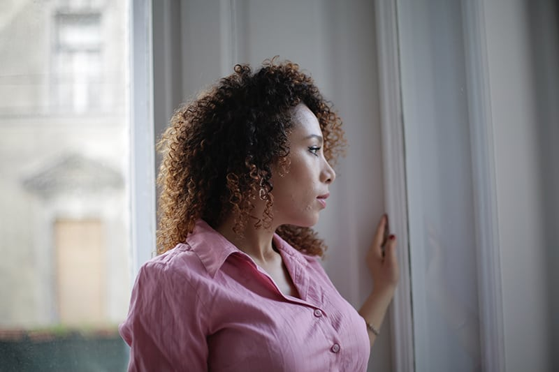 nachdenkliche Frau, die zu Hause durch das Fenster schaut