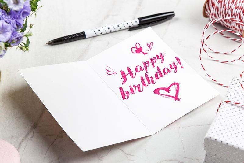 offene Geburtstagsgrußkarte in der Nähe des Stiftes
