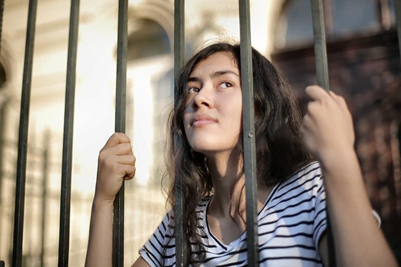 traurige isolierte Frau, die durch einen Zaun wegschaut, während sie ihr Gesicht darauf stützt