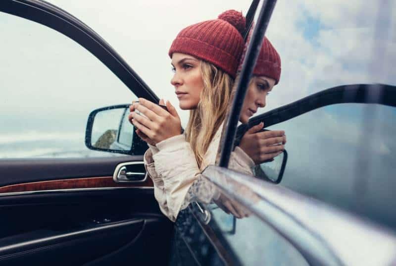schöne junge Frau, die in einem Auto sitzt