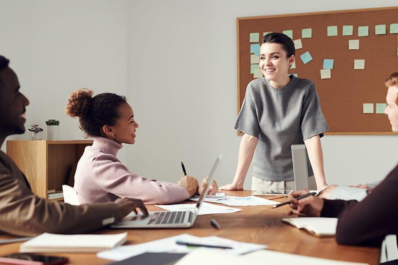 selbstbewusste Geschäftsfrau, die vor Kollegen im Besprechungsraum steht