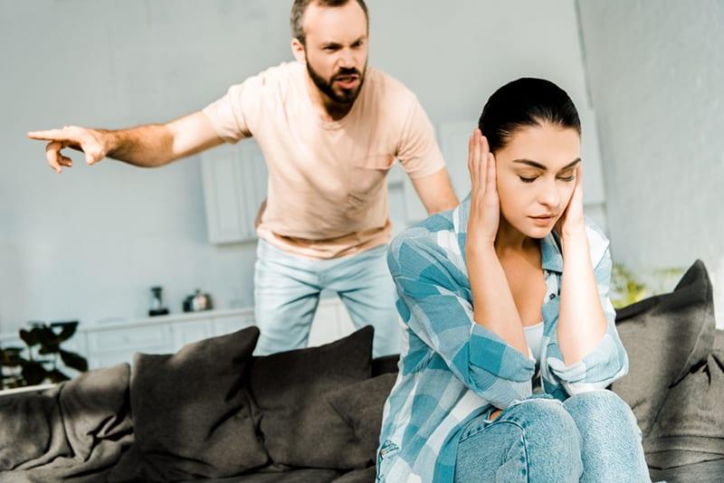 wütender Ehemann schreit Frau an, die auf dem Sofa sitzt und sie beleidigt