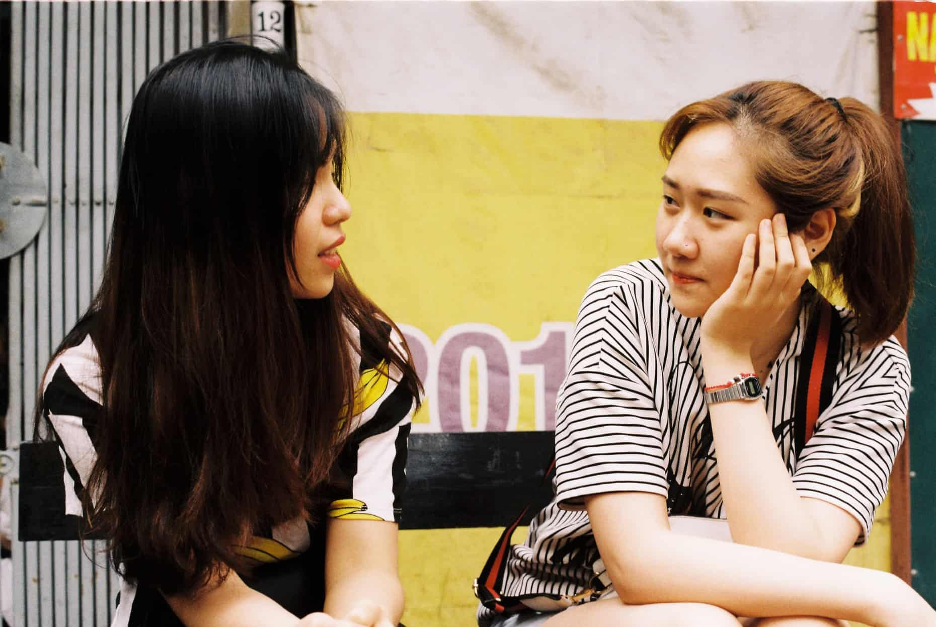 zwei Frauen, die sich gegenseitig die Augen ansehen, während sie auf der Bank sitzen