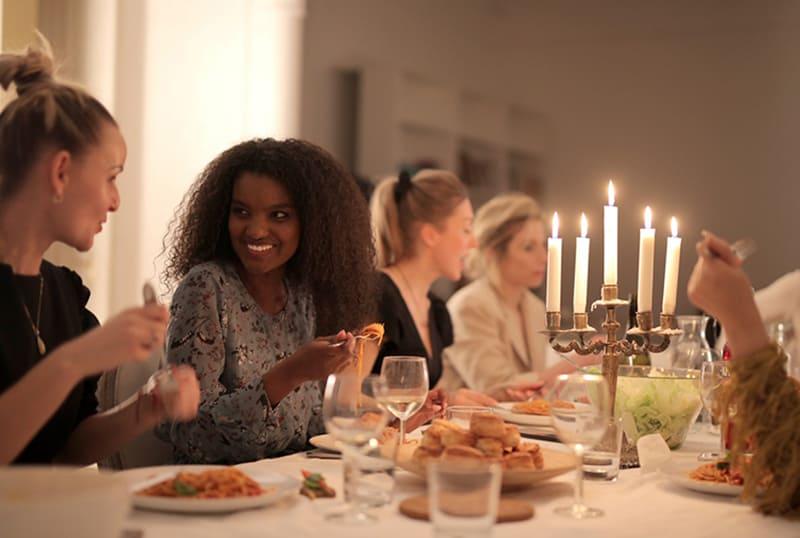 zwei Frauen unterhalten sich während des Abendessens, während sie nebeneinander sitzen