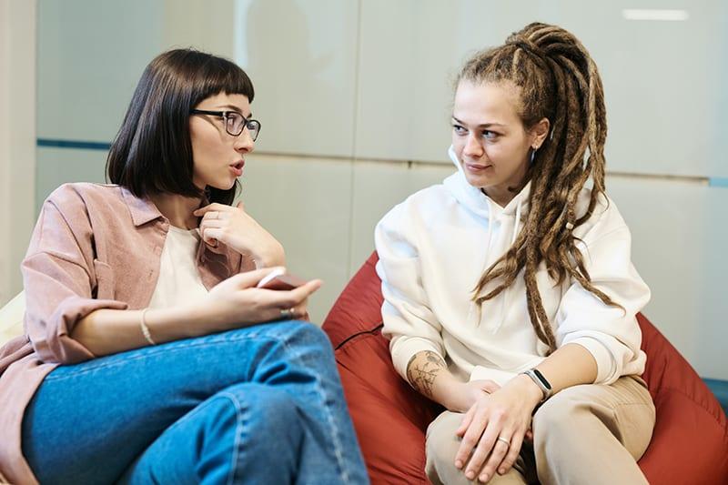 Zwei Frauen unterhalten sich, während sie sich gegenüberstehen und in einer faulen Tasche sitzen
