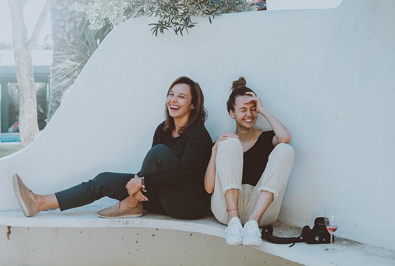 zwei Freundinnen sitzen auf der weißen Bank und lachen