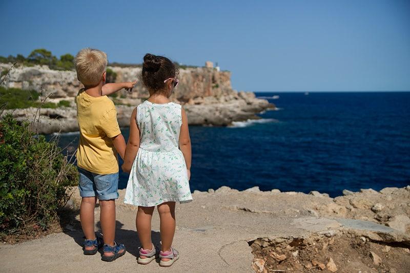 zwei Kinder, die Hände halten und auf der Klippe stehen, während sie das Meer beobachten