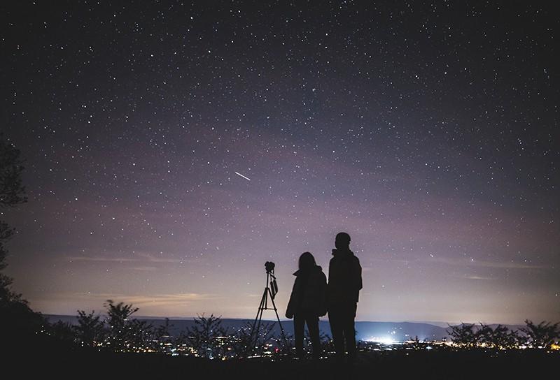 zwei Leute, die in der Nacht stehen und den Sternenhimmel beobachten