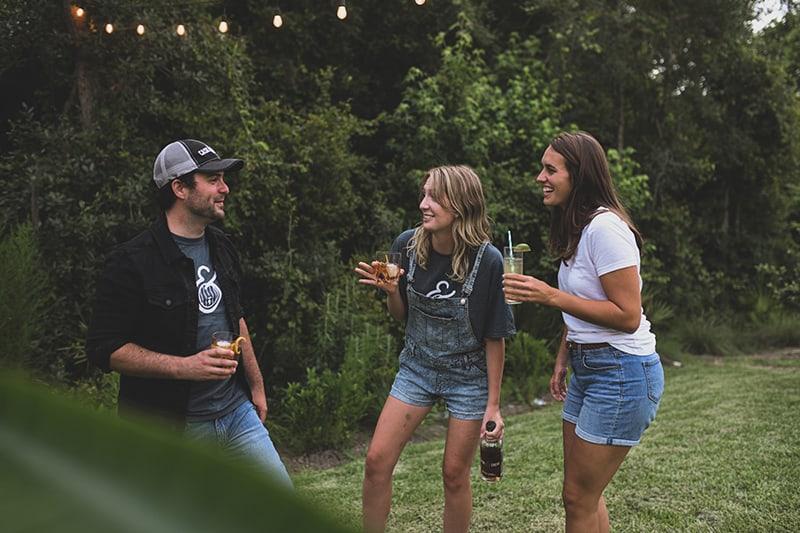zwei Mädchen sprechen mit einem introvertierten Mann, während sie zusammen auf einer Party etwas trinken