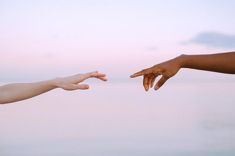 Zwei Personen erreichen sich bei Sonnenuntergang gegenseitig die Hand