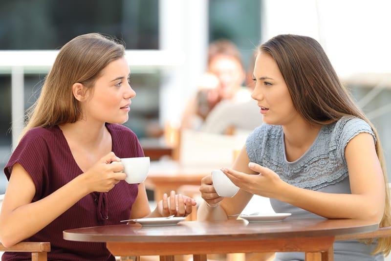 Zwei ernsthafte Freunde unterhalten sich beim Kaffeetrinken im Café