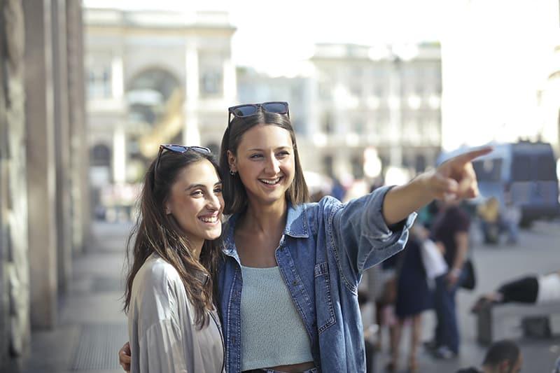 zwei lächelnde Frauen stehen auf der Straße, während eine mit einem Finger irgendwo zeigt