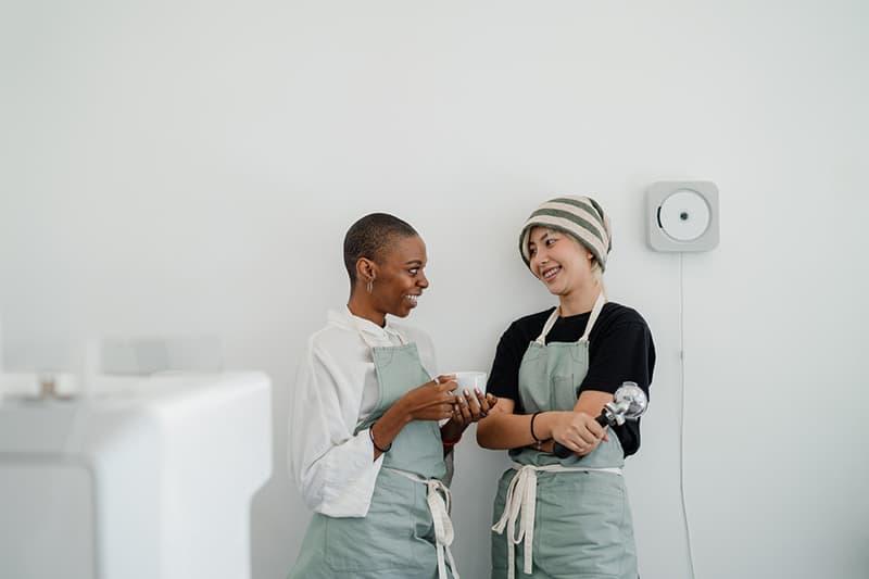 zwei lächelnde Frauen, die bei der Arbeit miteinander sprechen