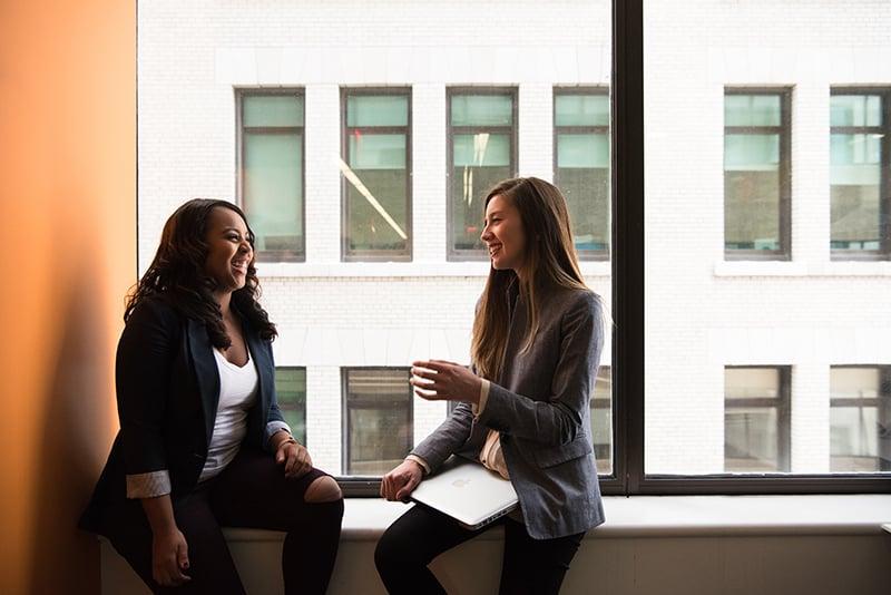 Zwei lächelnde Frauen sitzen in der Nähe des Fensters, während sie sich unterhalten