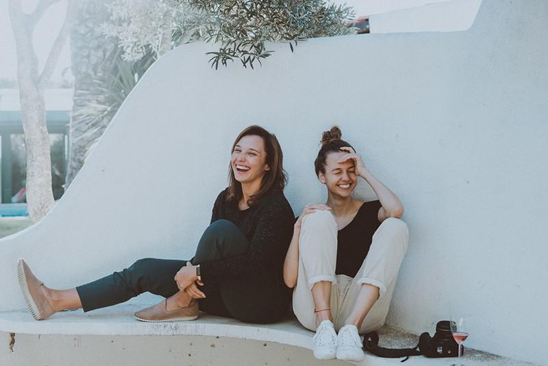 zwei lachende Freunde sitzen auf der weißen Bank, während sie Zeit miteinander verbringen