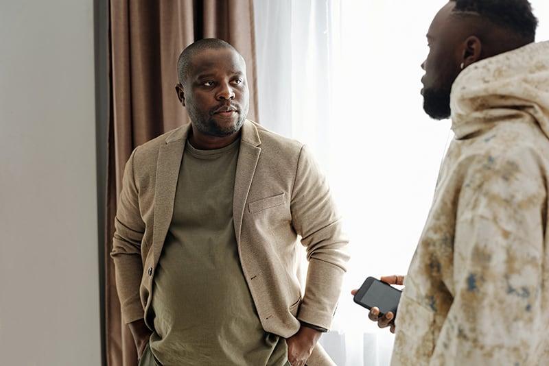 Zwei männliche Freunde unterhalten sich, während sie in der Nähe des Fensters im Haus stehen