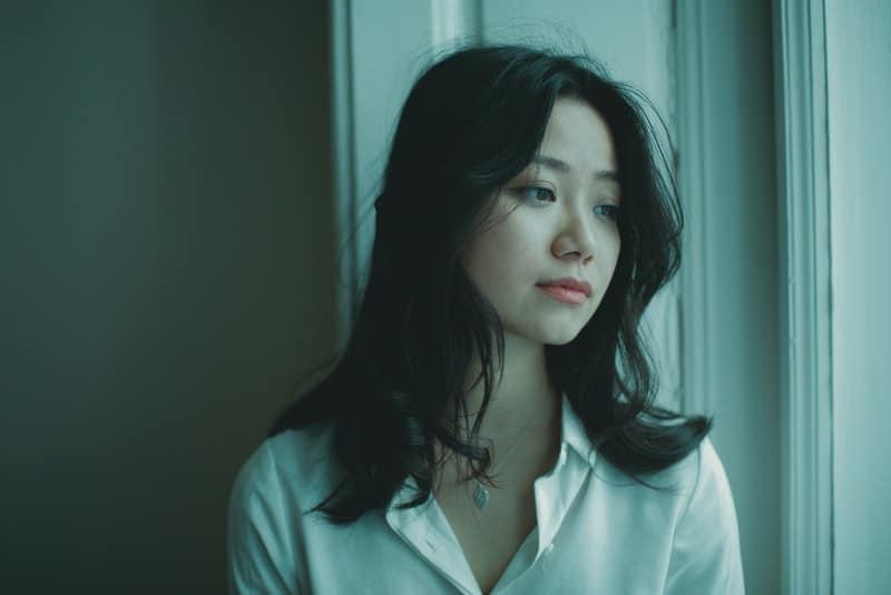 Am Fenster steht eine traurige Chinesin in einem weißen Hemd