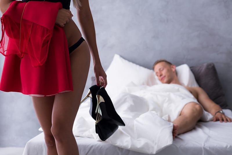 Attraktive Frau in Unterwäsche, die ihr rotes Kleid und ihre hohen Absätze hält, während sie vom Mann geht, der im Bett schläft